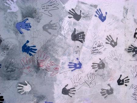 bocetos de personas: Berlín, Alemania, 20 febbraio 2011: parte del muro que dividió Berlín, huellas de manos que las personas que han dejado en el tiempo, en los bocetos pintados del color de fondo claro.