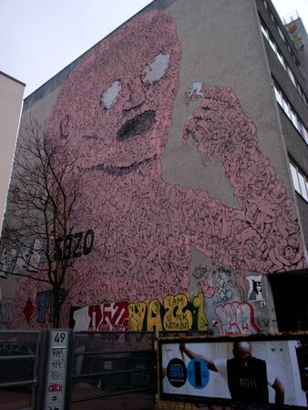 without windows: berlin,germany,20 february 2011: a building with an exterior wall without windows, in their place we see a mural of a giant pink. a man with two large white balls for eyes, a man formed by many little men in his image and likeness. Editorial