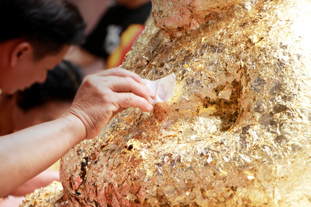 Hand of people are putting gold leaf Buddha sculpture for faith is symbol Buddhism, Religion concept