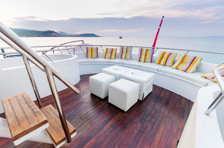 Yacht deck setup with white furnitures preparing for a group party. Stock Photo
