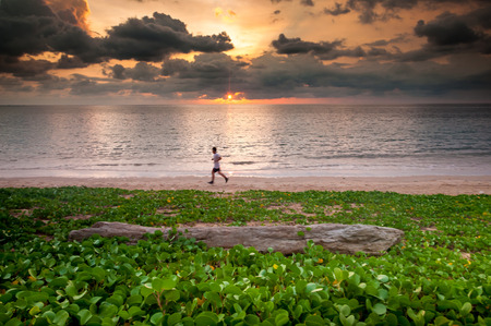 Sunset at behind a man joggin on the beach with log wood and beach morning glory photo