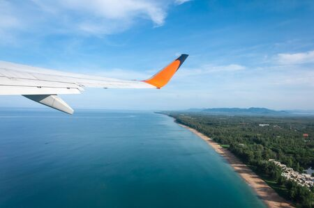 depart: Airplane taking off from the island with long beach underneath Stock Photo