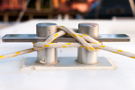 belay: White and yellow stripe rope on the belay at the marina Stock Photo