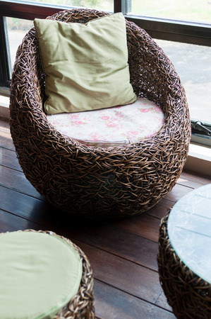 Vine weave chair in a cafe with small light green pillow