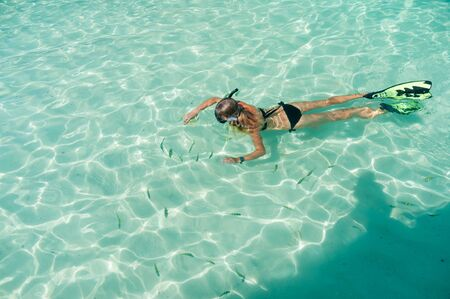 Girl snorkeling in a shallow water with fish Phi phi Thailand