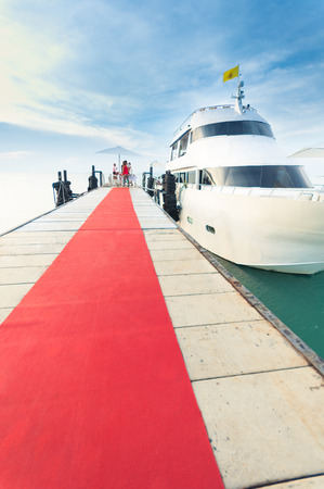 Yacht docking at the pier with red carpet to party on board Zdjęcie Seryjne