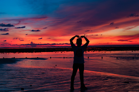 Man silhouette formed his arms as heart shape at the beach with sunset behind photo