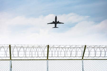 barbed wire fence: Airplane taking off from the airport over the fence of high security zone in Phuket , Thailand