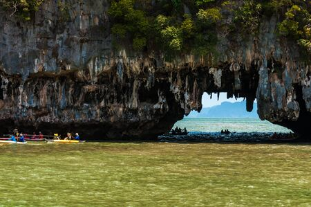 limestone caves: Tourists visit the limestone caves in the islands called Tham lod near Phuket. This is a popular tourist destination and the limestone rocks caves can only be entered from the sea with canoes.