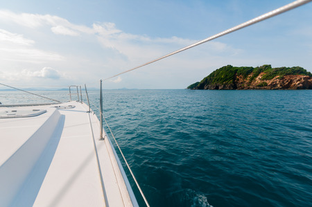 island: Private catamaran boat sailing to the island ahead. Luxury Lifestyle. Traveling on a yacht Stock Photo