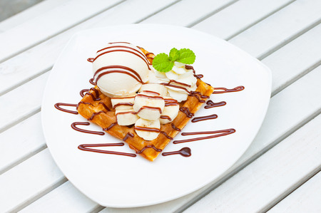 decorate: Vanilla ice cream waffle banana with chocolate sauce and mint leaf decorate on top  serve on white plates over the white wooden table