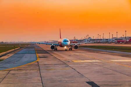 Airplane ready to taking off runway at the sunset time in the evening