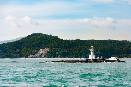 Small white Lighthouse on a sunny day in Phuket, Thailand with blue sky