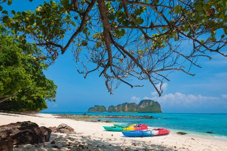 Colorful kayaks on sandy beach by crystal blue sea in Phuket, Thailand