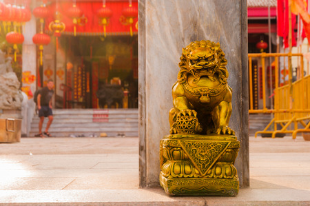 Golden chinese lion guardian sculpture in front of the gate to the temple Zdjęcie Seryjne - 54124885