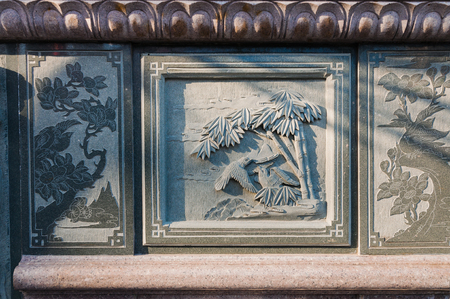 bas: Chinese bas relief art in a wall with evening light
