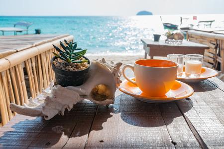 サトゥン タイ ・ リペ島の美しい朝の日差しのビーチの前に木製のテーブルの上にコーヒー カップ