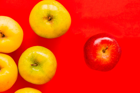 loner: One red apple standing out from a group of other apples on a red background from the crowd, leadership, difference concept, Selective focus