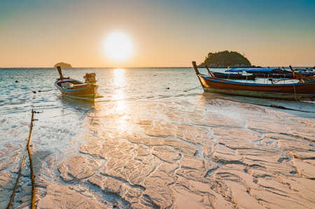 Beach in the morning sunrise with beautiful texture on the beach and traditional longtail boats in Lipe island, Satul, Thailand