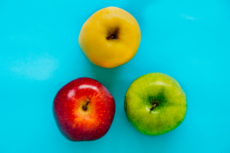 Top view of Red, green and yellow apple different in colors on a blue background ,Diversity Concept