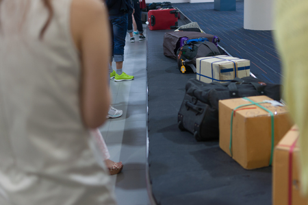 Line of luggage and belonging and people waiting for claims on arrival flight at the airports carousel Stock Photo