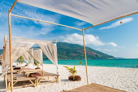 サンシャインの青い空の日に素敵なパビリオンで高級 VIP ビーチでリラックスします。