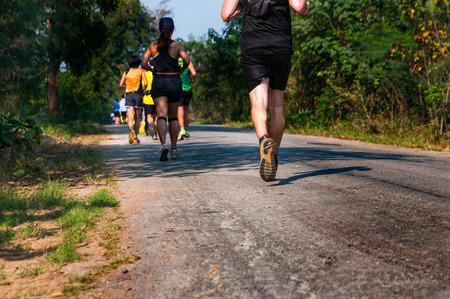 トレイル ランナーのスプリント レースの競争の最後の 1 マイルのための舗装道路に汗まみれの服を着て自分の実行