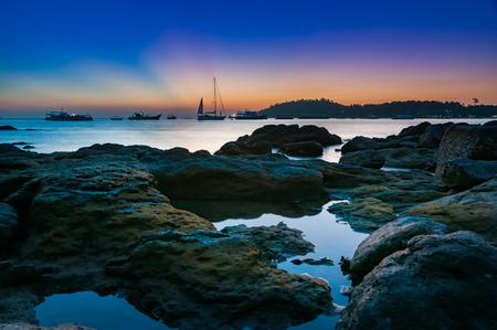 モーター ボートの岩と苔の小さな植民地のハイシーズンには穏やかな海でドッキングが覆われたカラフルな暗い夕暮れの海とヨットと日没後の空、 写真素材
