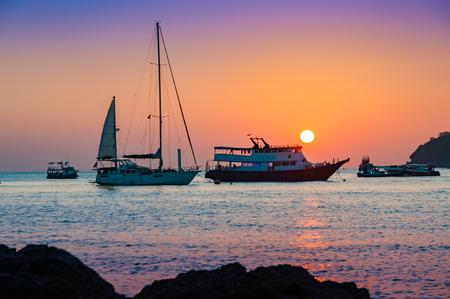 前面にドッキングする黄金の時間と穏やかな海でのモーター ボート、ヨット客船と色鮮やかな夕焼け 写真素材