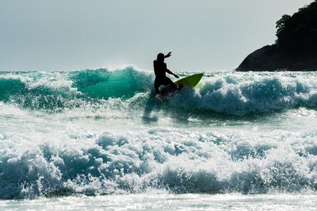 若いサーファー男は、カタビーチ, プーケット タイで大きな青い波の上の彼のサーフィンをお楽しみください。 写真素材