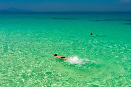 男とターコイズ ブルーの透き通った海は水の近くに、タイのプーケット島シュノーケ リング