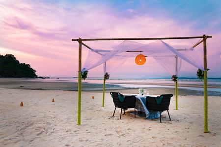 空の椅子のカップルのためのミステリーの中に熱帯のビーチでロマンチックな高級ディナー テーブルの設定 写真素材