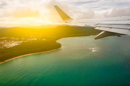 青いビーチ海島、翼、光フィルター、タイのプーケットでウィンドウから上空を飛んでいる飛行機