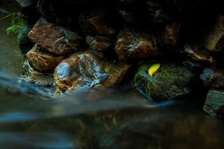 コピー スペースと長時間露光と暗い低キーの滝と岩の黄葉 写真素材