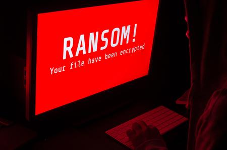 ランサムウェアとコンピューター画面攻撃赤と暗い部屋でキーボード、理想的なオンライン セキュリティとデジタル犯罪に合わせる男に警告 写真素材