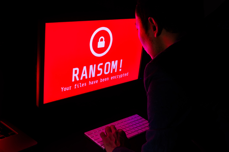 ランサムウェアの攻撃ファイルをコンピューターの画面は暗号化スーツがオンライン セキュリティとデジタル犯罪の理想的な暗い部屋でキーボード