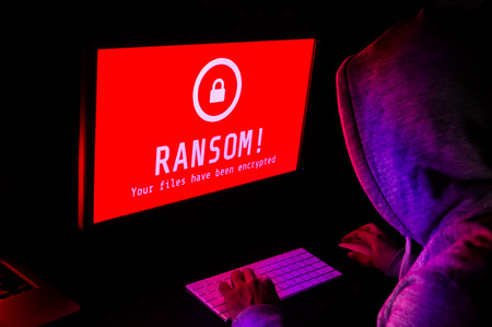 Computer screen with ransomware attack alert in red and a hacker man keying on keyboard in a dark room, ideal for online security failure and digital crime Stock Photo