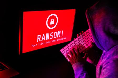 Computerscherm met ransomware aanval waarschuwing in rood en een hacker man intoetsen op toetsenbord in een donkere kamer, ideaal voor online veiligheidsuitval en digitale misdaden, lange blootstelling selectieve aandacht