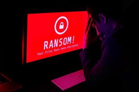 コンピューター画面で赤でランサムウェアの攻撃暗号化ファイル ・ アラートとスーツを着た男が長時間露光の選択と集中、デジタル犯罪オンライン