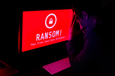 Computer screen with ransomware attack file encrypted alerts in red and a man in suit get stress with keyboard in a dark room, ideal for online security failure and digital crime, long exposure selective focus