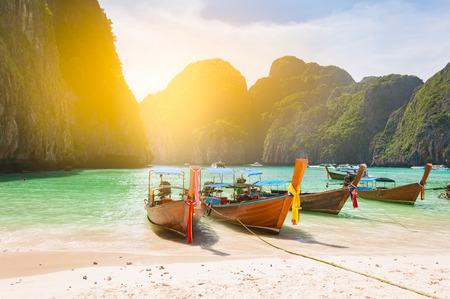 伝統的なロングテール ボート近くのプーケット島タイのクラビではっきりと砂浜のビーチの目の前でマヤ湾にドッキング光フィルター