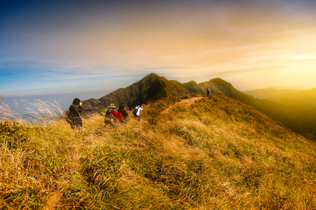 Group of tourists enjoy hiking on the top of mountain with amazing scenic of changpuek mountain in Kanchanaburi, Thailand; Gold light filtered Zdjęcie Seryjne - 78763025