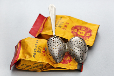 Tea bags and tea scoop on white background