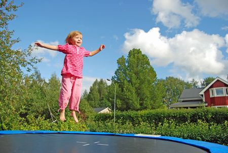 Girl jumping on the trampolin photo