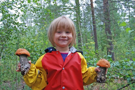 Girl with mushroom in the forest Фото со стока
