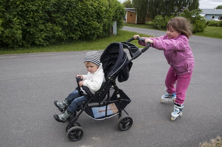 Sister and brother walking with stroller and rollers photo
