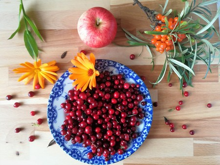 Ripe fresh cowberry (lingonberry, partridgeberry, foxberry) in bowl on table from above.