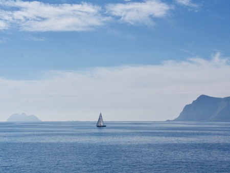 Yacht at the berth in the Norwegian fjord on a background of blue sky and sea landscape