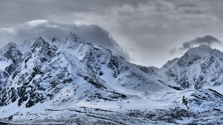 Power of snow cowered mountains in Norway, fog in the morning, may Фото со стока