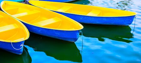 Blue and yellow rowboats anchored at jetty